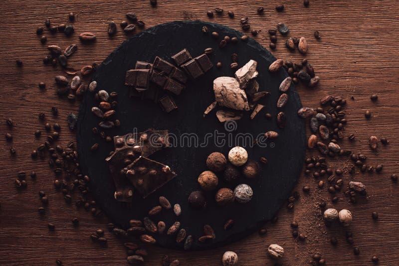 högstämd sikt av skärbrädan med olika typer av chokladstycken och tryfflar som omges av kakaobönor, kaffekorn och arkivfoto