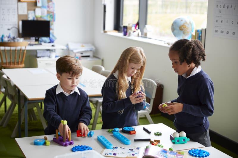 Högstämd sikt av tre grundskola för barn mellan 5 och 11 årungar som arbetar tillsammans genom att använda konstruktionskvarter i royaltyfria bilder