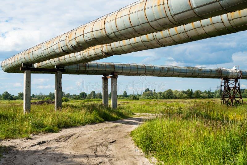 Högstämt avsnitt av rörledningarna ovanför grusvägen royaltyfria foton