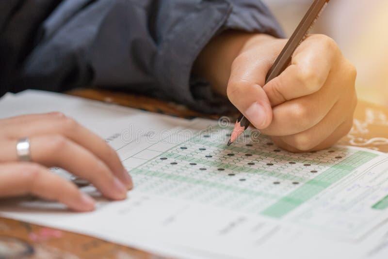 Högstadium- eller universitetsstudenthänder som tar examina som skriver undersökning på pappers- optisk form för svarsark av det  royaltyfria bilder