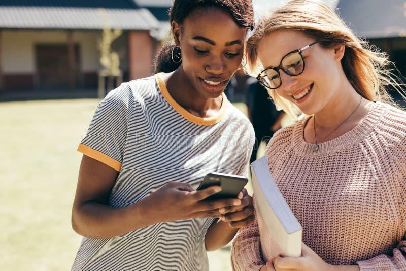 Högstadiumflickor på högskolauniversitetsområdet med den smarta telefonen royaltyfri fotografi