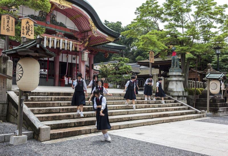 Högstadiumflickor som bär skolalikformig på den Fushimi Inari shrinen arkivbilder