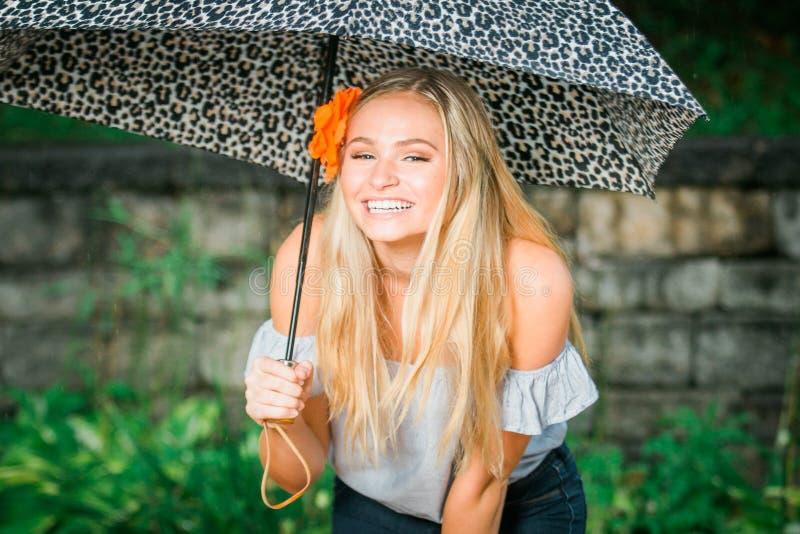 Högstadiumpensionären poserar med paraplyet för stående på ett regnigt royaltyfria foton