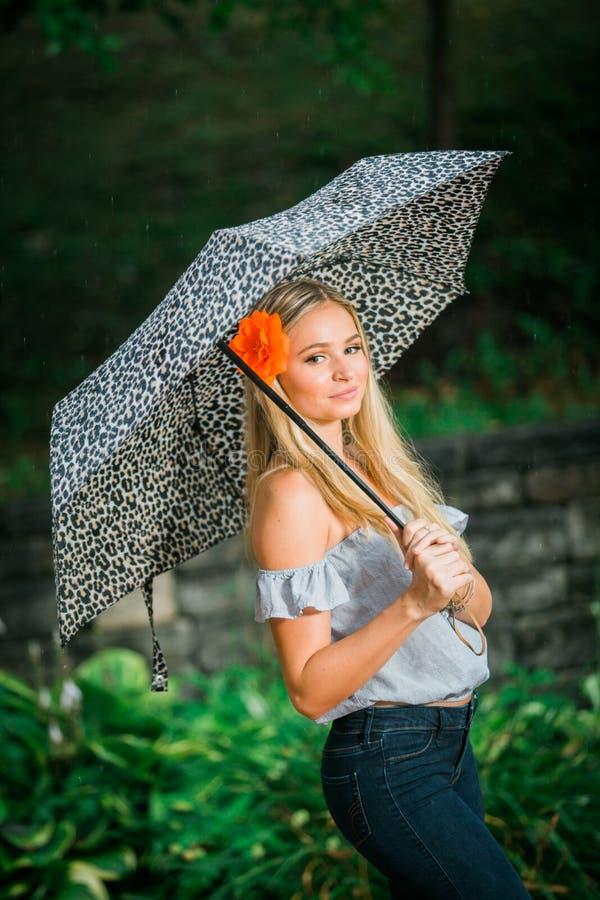 Högstadiumpensionären poserar med paraplyet för stående på ett regnigt royaltyfri fotografi