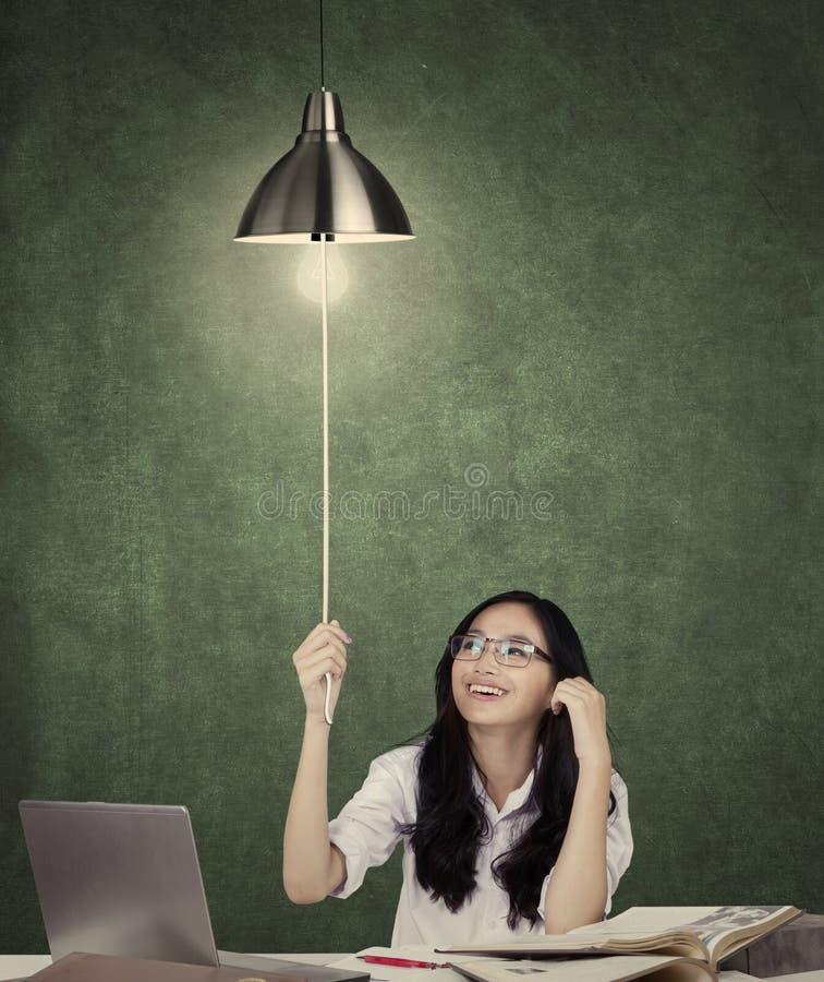 Högstadiumstudenten vänder på en lightbulb arkivfoto