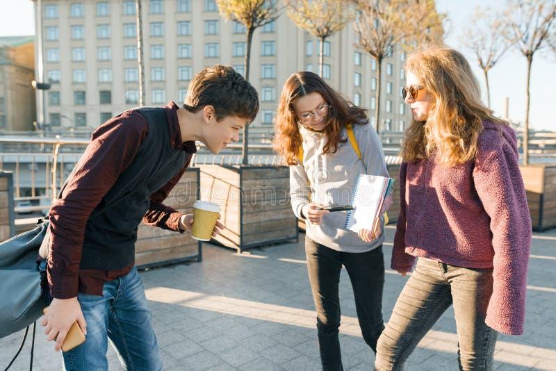 Högstadiumstudenter är utomhus- samtal Flickatonåringvisning på ett rent vitt ark i anteckningsboken och pojken som ser antecknin royaltyfri bild