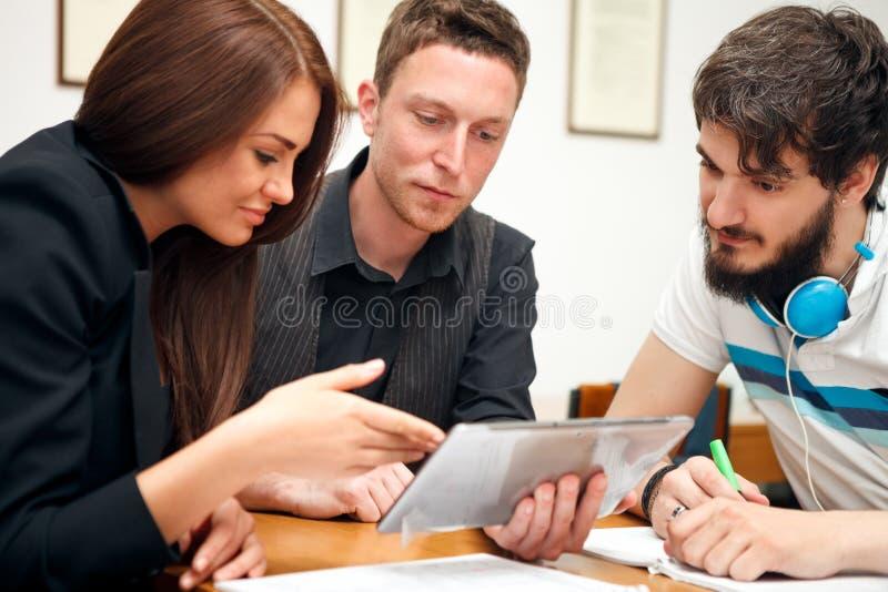 Högstadiumstudenter som använder minnestavladatoren arkivbild