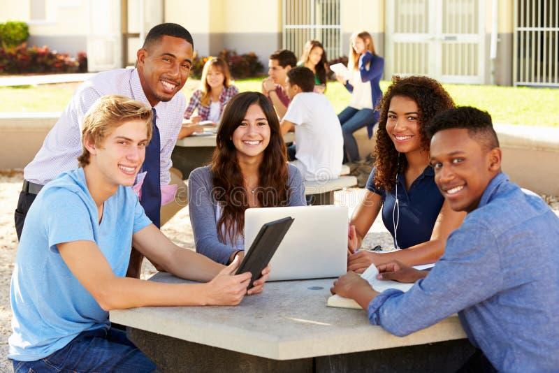 Högstadiumstudenter som arbetar på universitetsområde med läraren royaltyfri foto