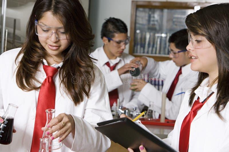 Högstadiumstudenter som för experiment arkivfoto