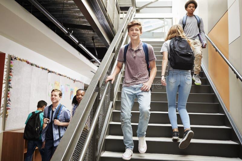 Högstadiumstudenter som går ner trappa i upptagen högskolabyggnad royaltyfria bilder