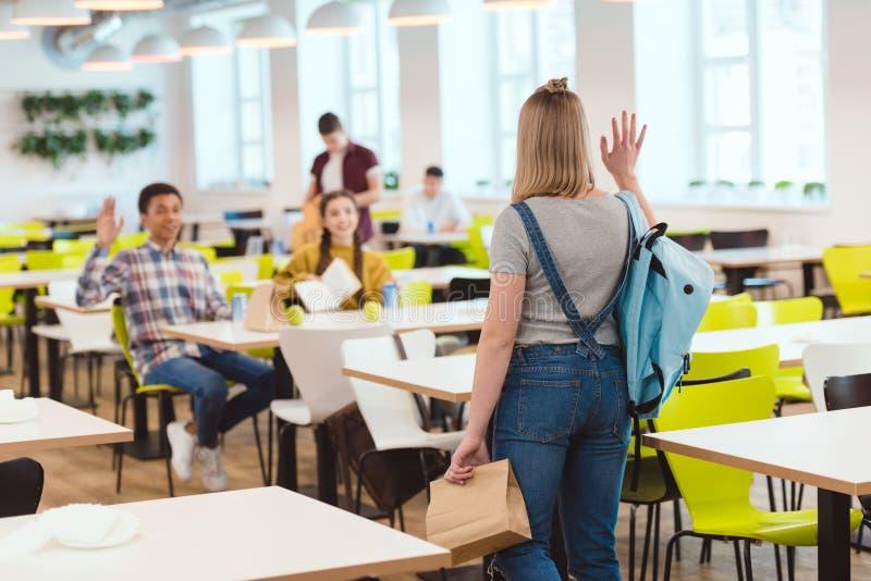 högstadiumstudenter som hälsar deras klasskompis arkivfoto