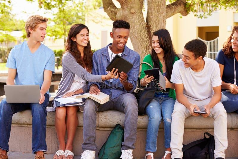 Högstadiumstudenter som samarbetar på projekt på universitetsområde arkivfoton