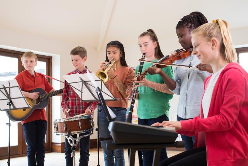 Högstadiumstudenter som spelar i skolaorkester tillsammans royaltyfria bilder