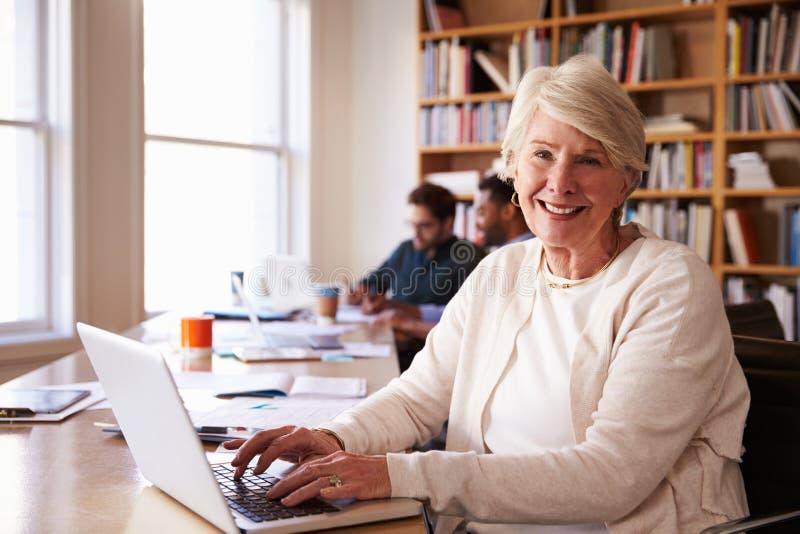 Högt affärskvinnaUsing Laptop At skrivbord i upptaget kontor arkivfoto