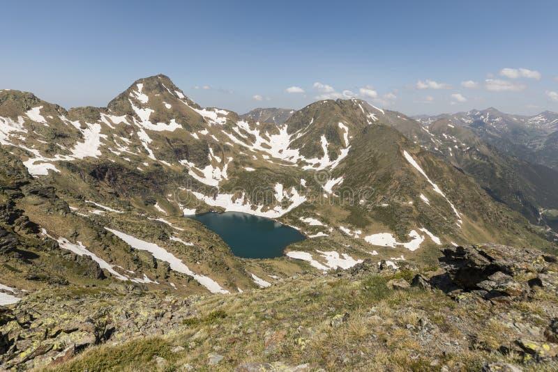 Högt alpint landskap med snöfält och sjöar i regionen Ordino i Andorra arkivbild