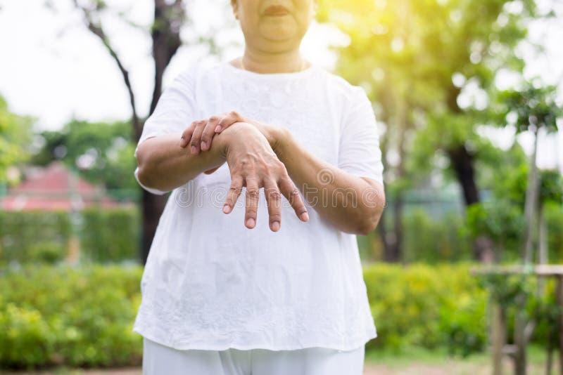 Högt asiatiskt kvinnligt lidande med parkinsons tecken för sjukdom royaltyfri bild