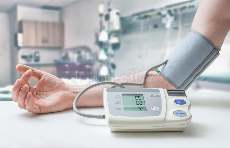 Högt blodtryckbegrepp Mannen mäter blodtryck med bildskärmen i sjukhus royaltyfri foto