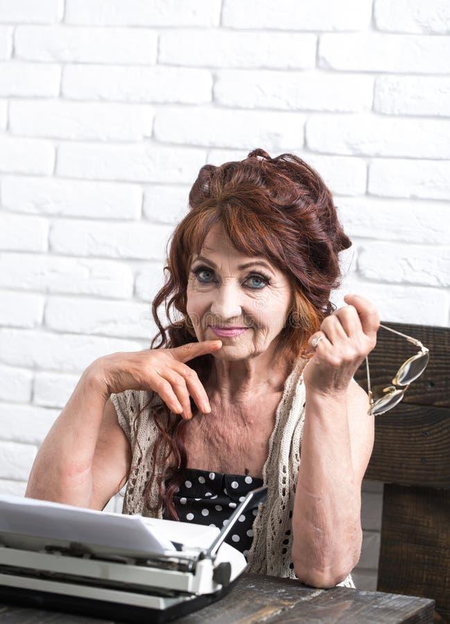 Högt erfaret Hög författare på skrivbordet Gammal reporter- eller journalisthandstil på skrivmaskinen Arbete för gammal kvinna i  royaltyfria foton