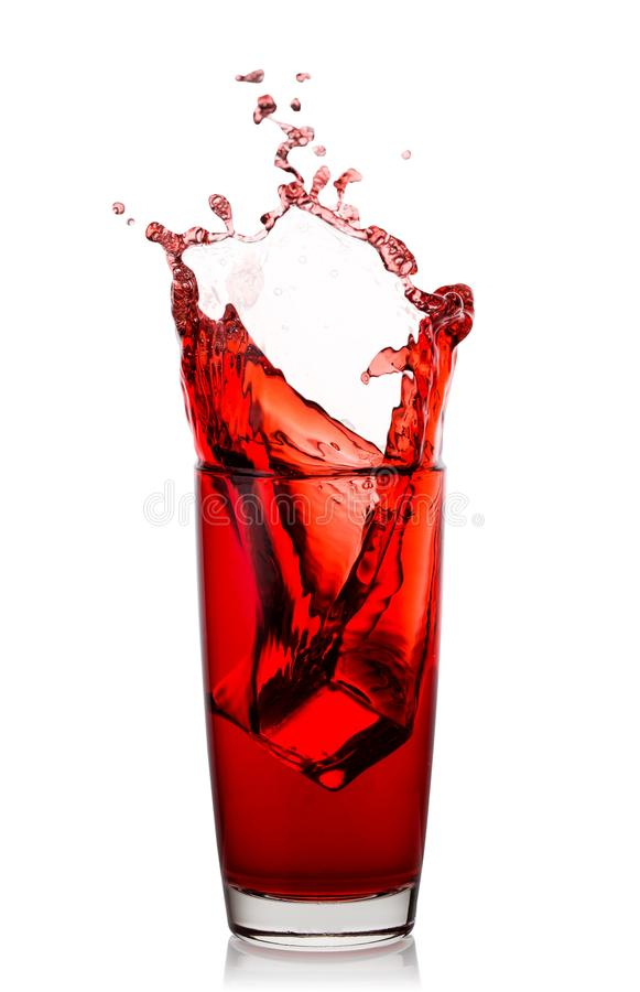 Högt exponeringsglas med färgstänk av naturlig körsbärsröd fruktsaft fotografering för bildbyråer