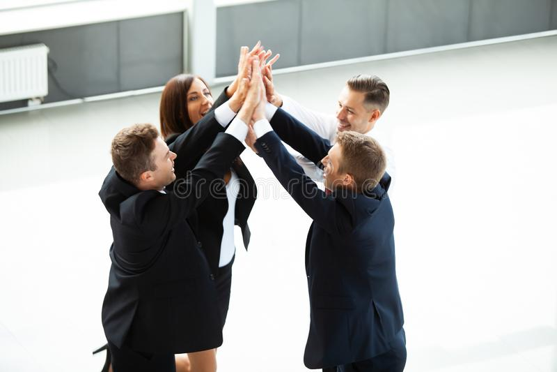 Högt-fem! gladlynt ungt ge sig för affärsfolk som är högt-fem medan deras kollegor som ser dem, och le arkivfoton