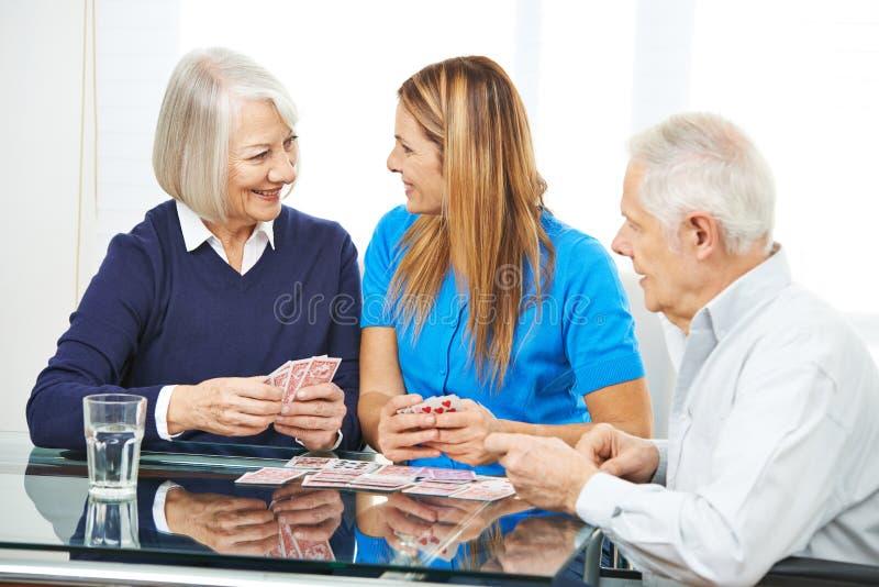 Högt folk som spelar kort tillsammans i vårdhem arkivfoto