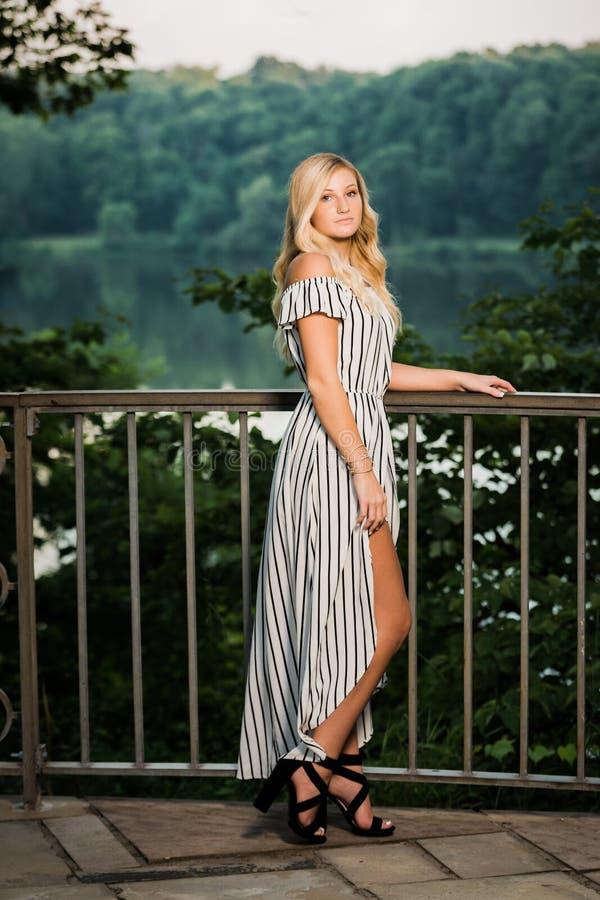 Högt foto för högstadium av blond Caucasian flickadet fria i Romperklänning royaltyfri foto