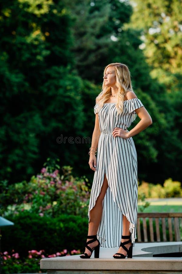 Högt foto för högstadium av blond Caucasian flickadet fria i Romperklänning royaltyfria bilder