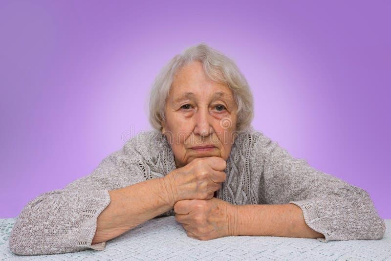 Högt grått haired drömma för kvinna som isoleras på blå bakgrund royaltyfria bilder