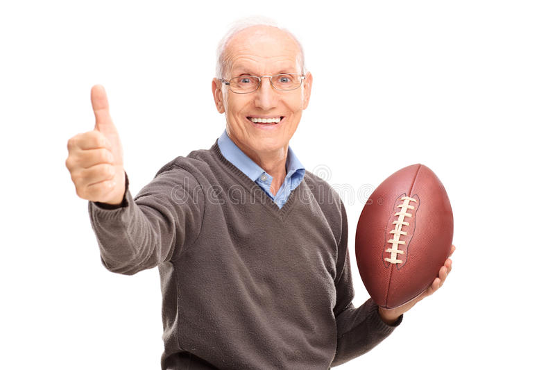 Högt innehav en fotboll och en ge sigtumme upp arkivfoto