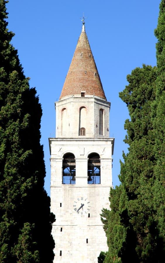 Högt Klocka torn av den forntida staden av AQUILEIA bland högväxt cypre royaltyfri foto