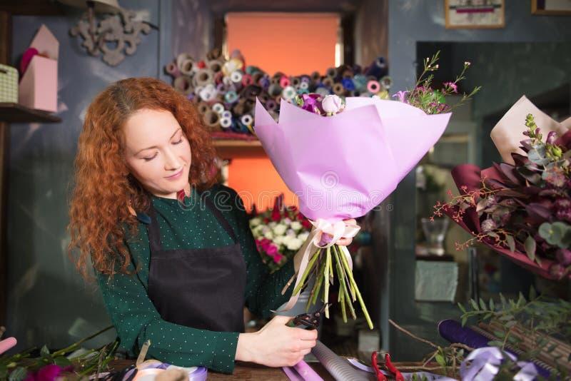 Högt kompetent blomsterhandlare som klipper en blommastjälk royaltyfri fotografi