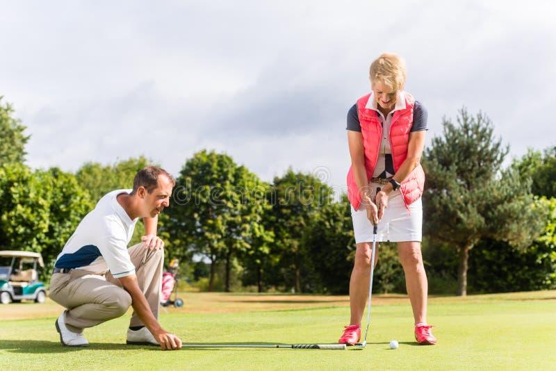Högt kvinna- och golfpro- öva deras sport arkivfoto