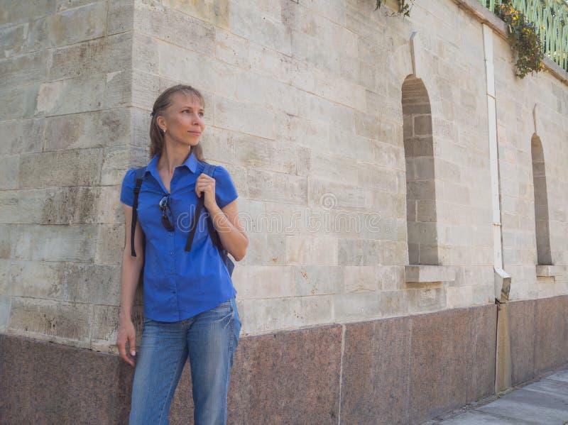 Högt kvinnaanseende mot den forntida väggen royaltyfri foto