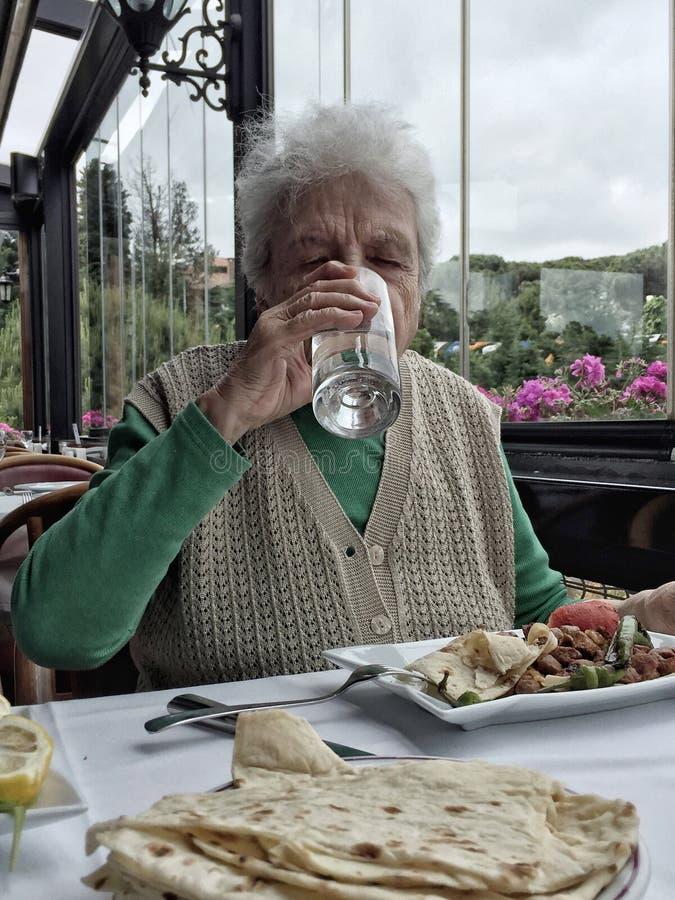 Högt kvinnadricksvatten, medan ha lunch i en restaurang royaltyfri bild