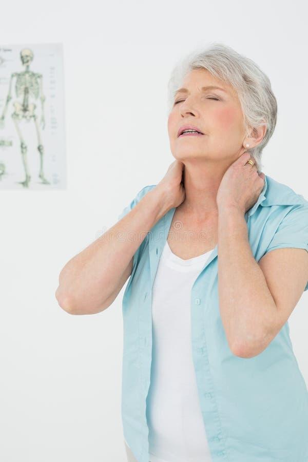 Högt kvinnalidande från hals smärtar i medicinskt kontor royaltyfria foton