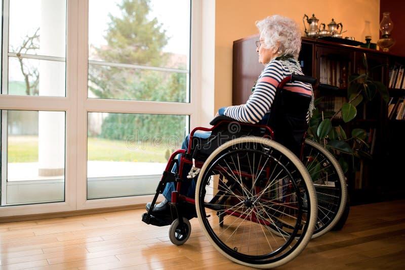 Högt kvinnasammanträde för ensamhet i rullstol på vårdhemmet royaltyfri bild