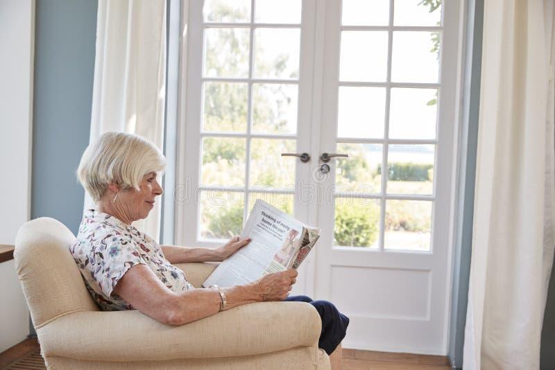 Högt kvinnasammanträde i fåtöljen som hemma läser en tidning fotografering för bildbyråer