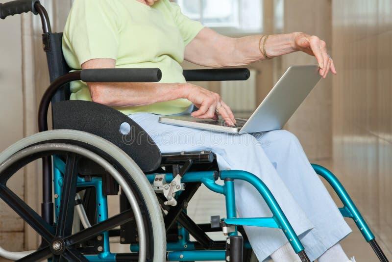 Högt kvinnasammanträde i rullstol genom att använda bärbara datorn royaltyfri foto