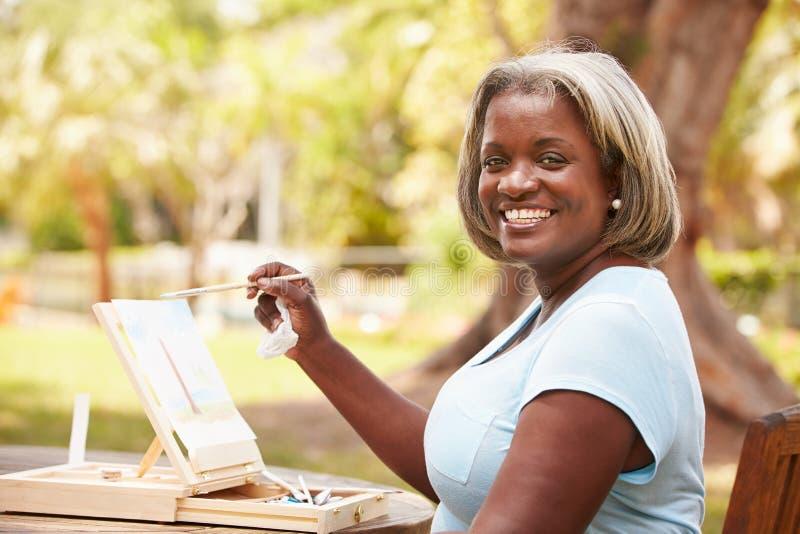 Högt kvinnasammanträde på det utomhus- tabellmålninglandskapet royaltyfri foto