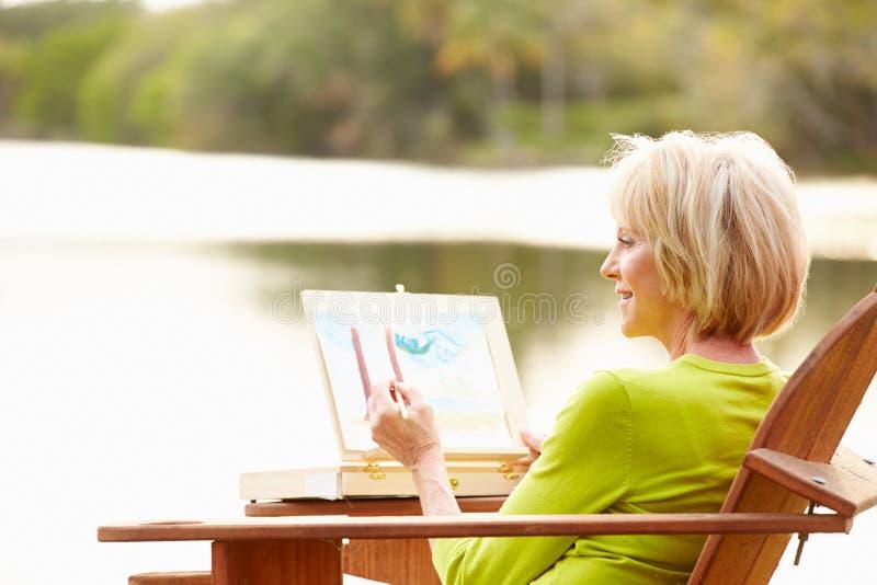 Högt kvinnasammanträde på det utomhus- tabellmålninglandskapet royaltyfria foton
