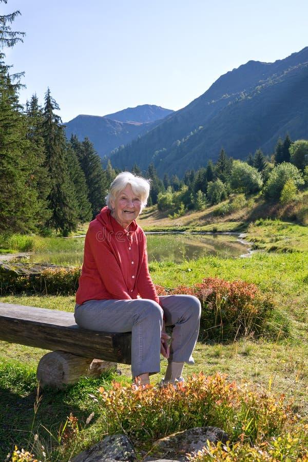 Högt kvinnasammanträde på en bänk i Schweiz fotografering för bildbyråer