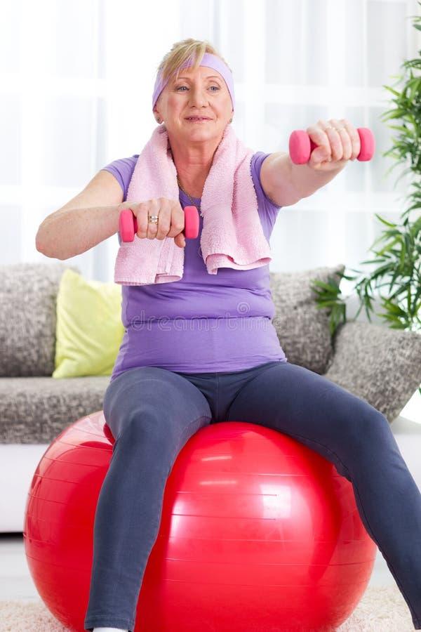 Högt kvinnasammanträde på idrottshallboll och övning med vikter på H royaltyfri foto