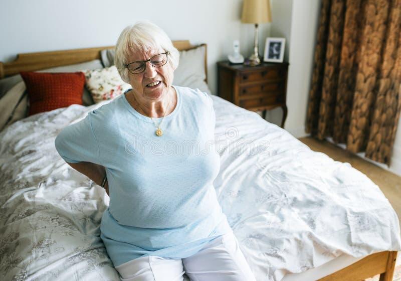 Högt kvinnasammanträde på sängen med tillbaka smärtar royaltyfria foton