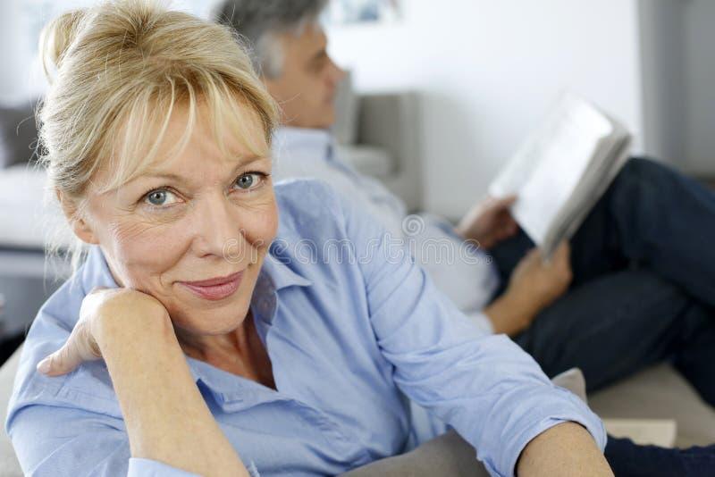 Högt kvinnasammanträde på soffan med makeläsning beside arkivfoto