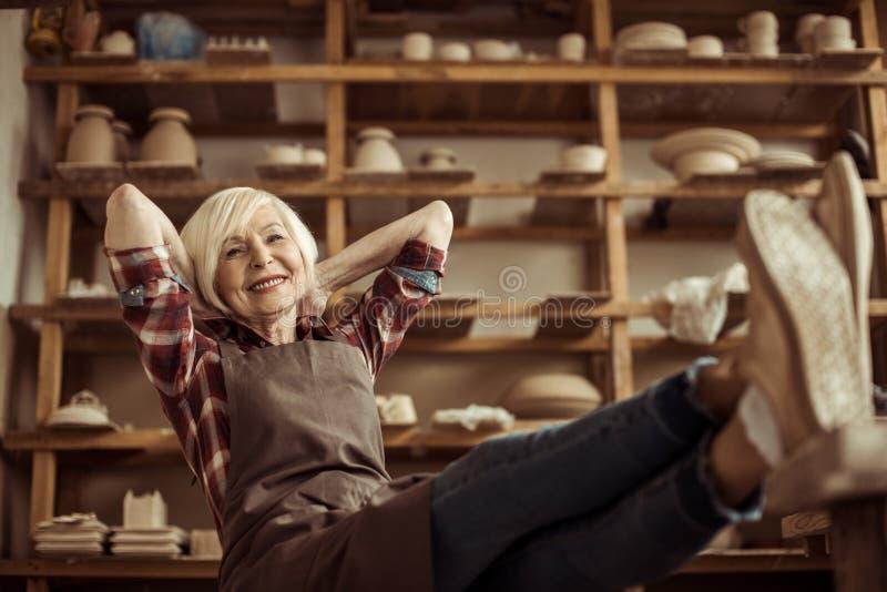 Högt kvinnasammanträde på stol med ben på tabellen mot hyllor med krukmakerigods arkivbild
