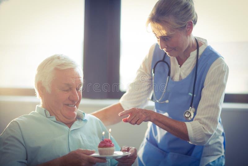 Högt kvinnligt fira för doktor som är högt, mans födelsedag i sjukhus arkivbilder
