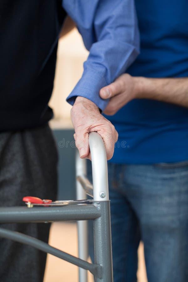 Högt Mans händer på att gå ramen med omsorgarbetaren i Backgrou royaltyfri fotografi