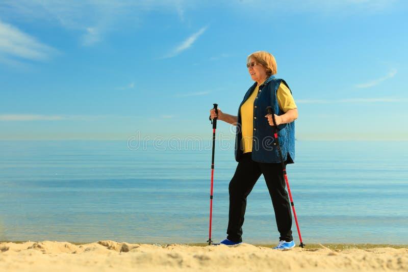 Högt nordiskt gå för aktiv kvinna på en strand fotografering för bildbyråer
