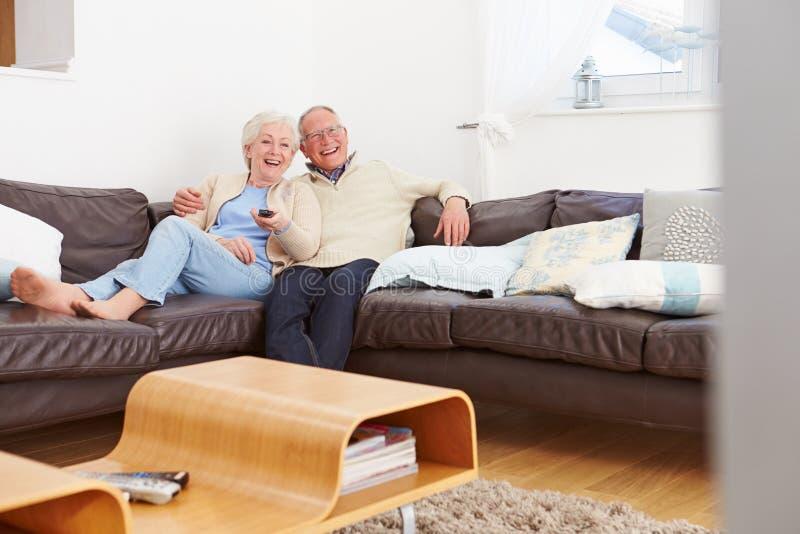 Högt parsammanträde på hållande ögonen på tv för soffa arkivbilder