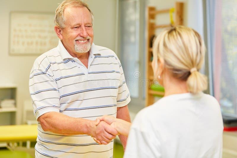 Högt som tacksamma tålmodiga skaka doktors hand royaltyfri bild